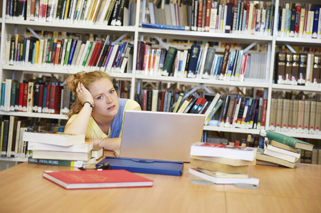 accomplishes: Bored young woman in library LANG_EVOIMAGES