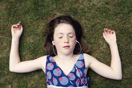 lays down: Girl lying on grass with earphones