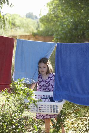 accountable: Young girl carrying the washing