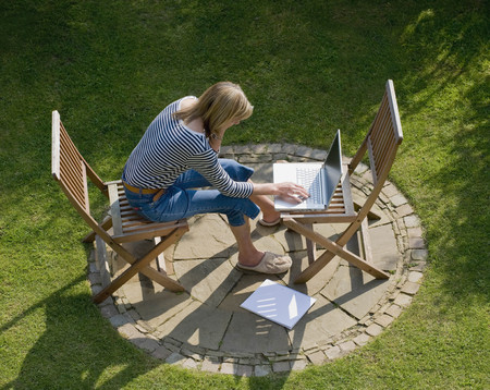 middlesex: Woman working on a laptop in the garden
