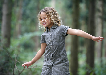 Young girl arms outstretched woodland