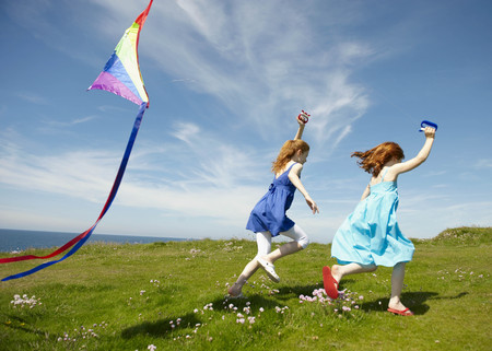 2 young girls running with kites