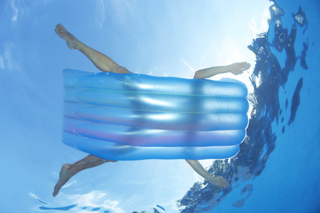 rejuvenated: Man on inflatable lilo in pool LANG_EVOIMAGES