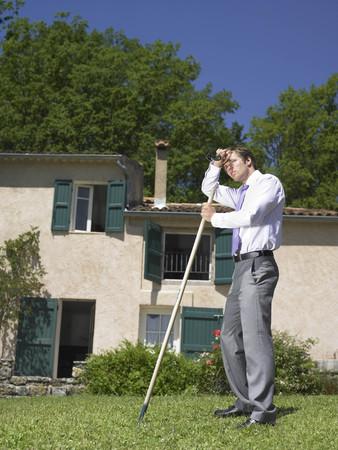 verticals: Suited man raking lawn