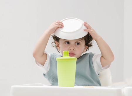A boy with his food bowl on his head. LANG_EVOIMAGES