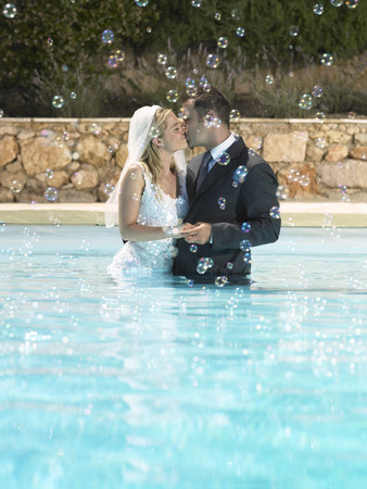 Bride and groom kissing in pool LANG_EVOIMAGES