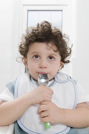 A boy sucking a spoon.