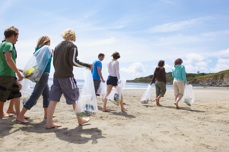 Young people collecting garbage on beach LANG_EVOIMAGES