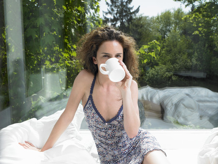 lavishly: Woman drinking in a cup, in bed LANG_EVOIMAGES