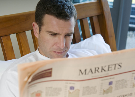 middlesex: Man reads financial paper in bed LANG_EVOIMAGES