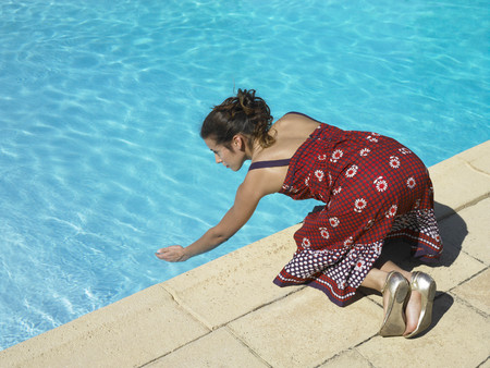 rejuvenated: Girl testing pool water LANG_EVOIMAGES
