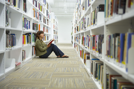 somber: Young woman sitting on library floor
