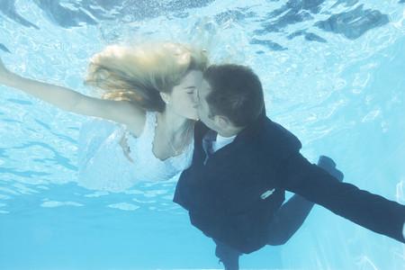saturating: Bride and groom kissing underwater