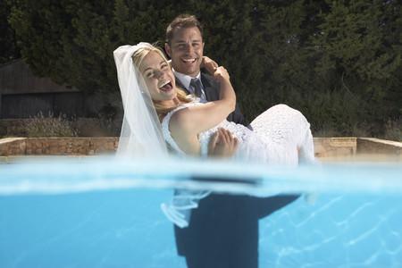 marrying: Groom carrying bride in pool