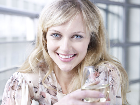 Woman smiling to camera with wine glass