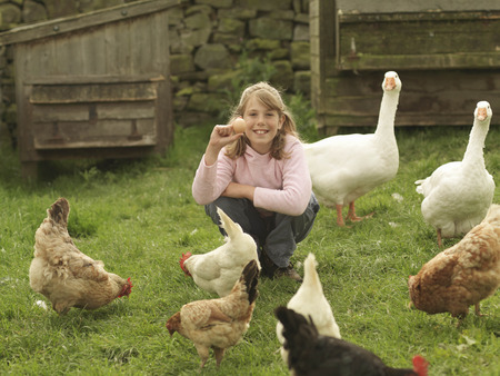 assembled: Girl Holding Egg With Hens And Geese LANG_EVOIMAGES