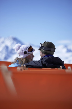 Couple sitting close in chair lift LANG_EVOIMAGES