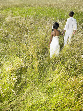 in twos: Married couple walking in a field