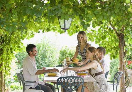 Groep genieten van maaltijd in de tuin LANG_EVOIMAGES