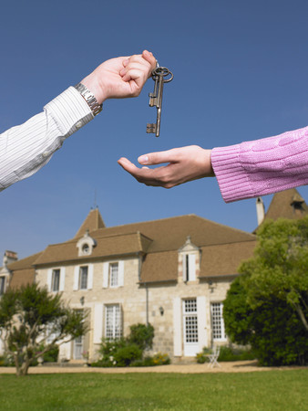 Woman receiving keys to country home LANG_EVOIMAGES