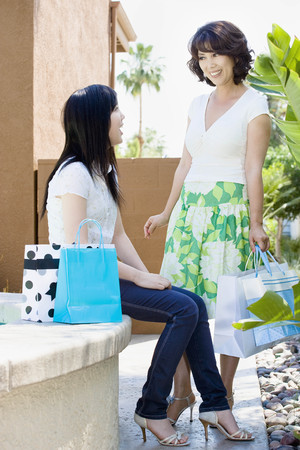 indebted: Mom and teen with shopping bags talking
