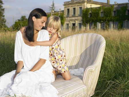 Mother and daughter on sofa in a field