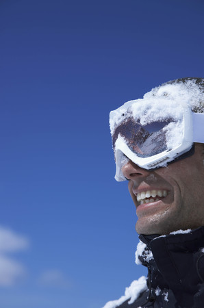 winter escape: Man laughing,  face covered with snow