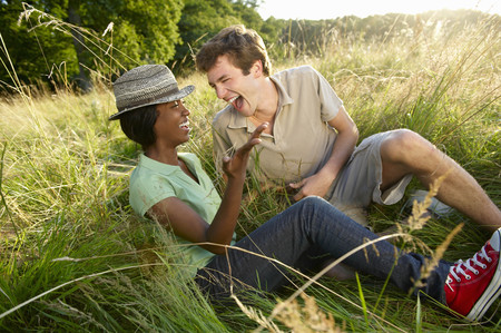 Couple laughing in a field LANG_EVOIMAGES