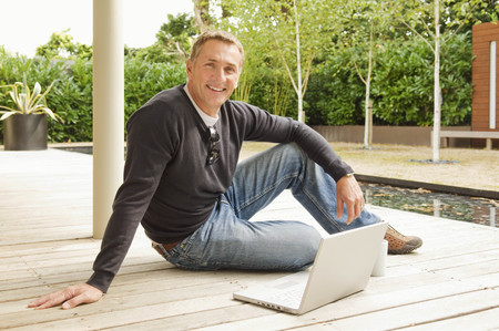 telecommuter: Businessman sitting outside smiling