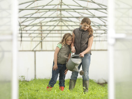 conservatories: Sisters Watering Crops In Polytunnel