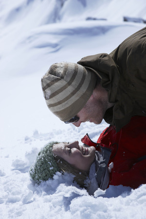 winter escape: Young couple lying in snow