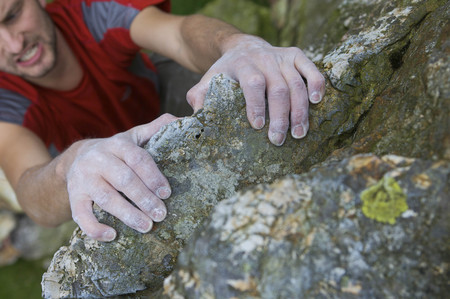 Climbers hands on a rock face.
