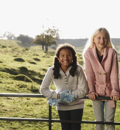leaning by barrier: Two girls on gate in countryside