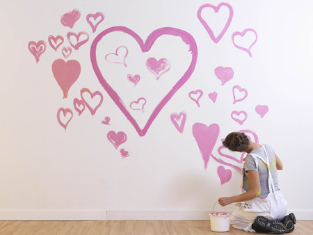 Girl paints pink hearts. LANG_EVOIMAGES