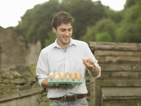 Farmer Looking At Tray Of Eggs