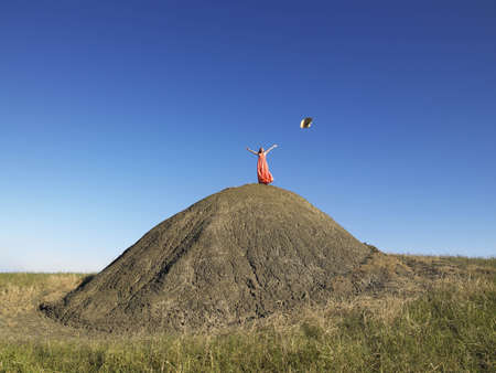 low spirited: Woman on top of hill throwing hat