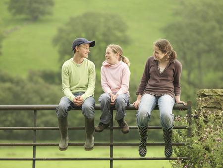 Boy And Girls Sitting On Gate