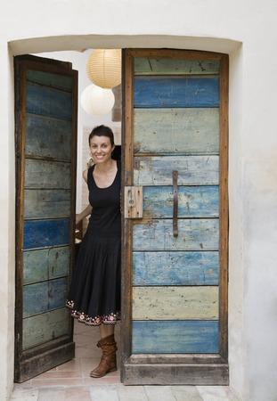 abodes: Woman peeking out door LANG_EVOIMAGES