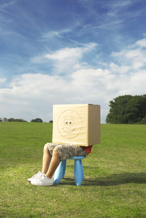 bashfulness: boy on stool with box on head