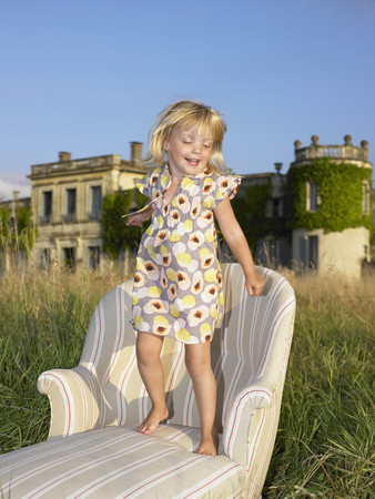 Girl jumping on sofa in a field