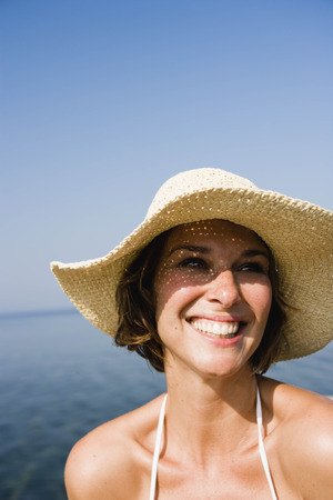 Woman with hat smiling LANG_EVOIMAGES