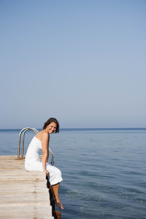 joyous: Woman sitting on a pier LANG_EVOIMAGES