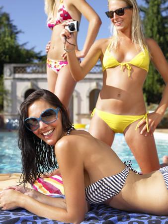 arrodillarse: Novias tomando fotos, junto a la piscina