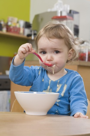 overflows: Young girl eating and spilling pudding LANG_EVOIMAGES