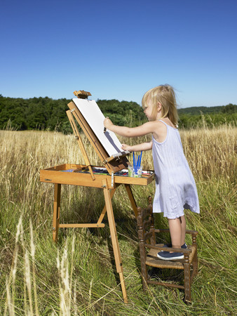 Girl painting in a field