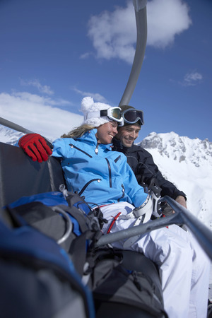 snows: Couple sitting close in chair lift LANG_EVOIMAGES