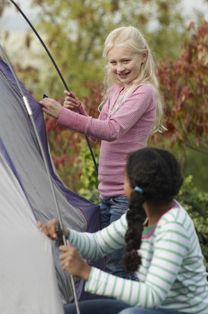 Two girls erecting tent LANG_EVOIMAGES