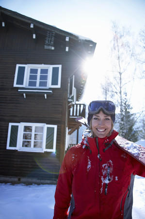 abodes: Young woman in front of chalet with ski