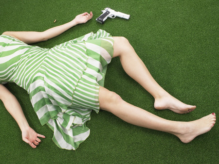 adverse: Woman lying on floor with gun LANG_EVOIMAGES