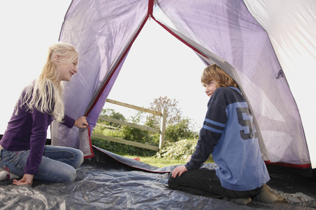slanting: Boy and Girl sitting in tent